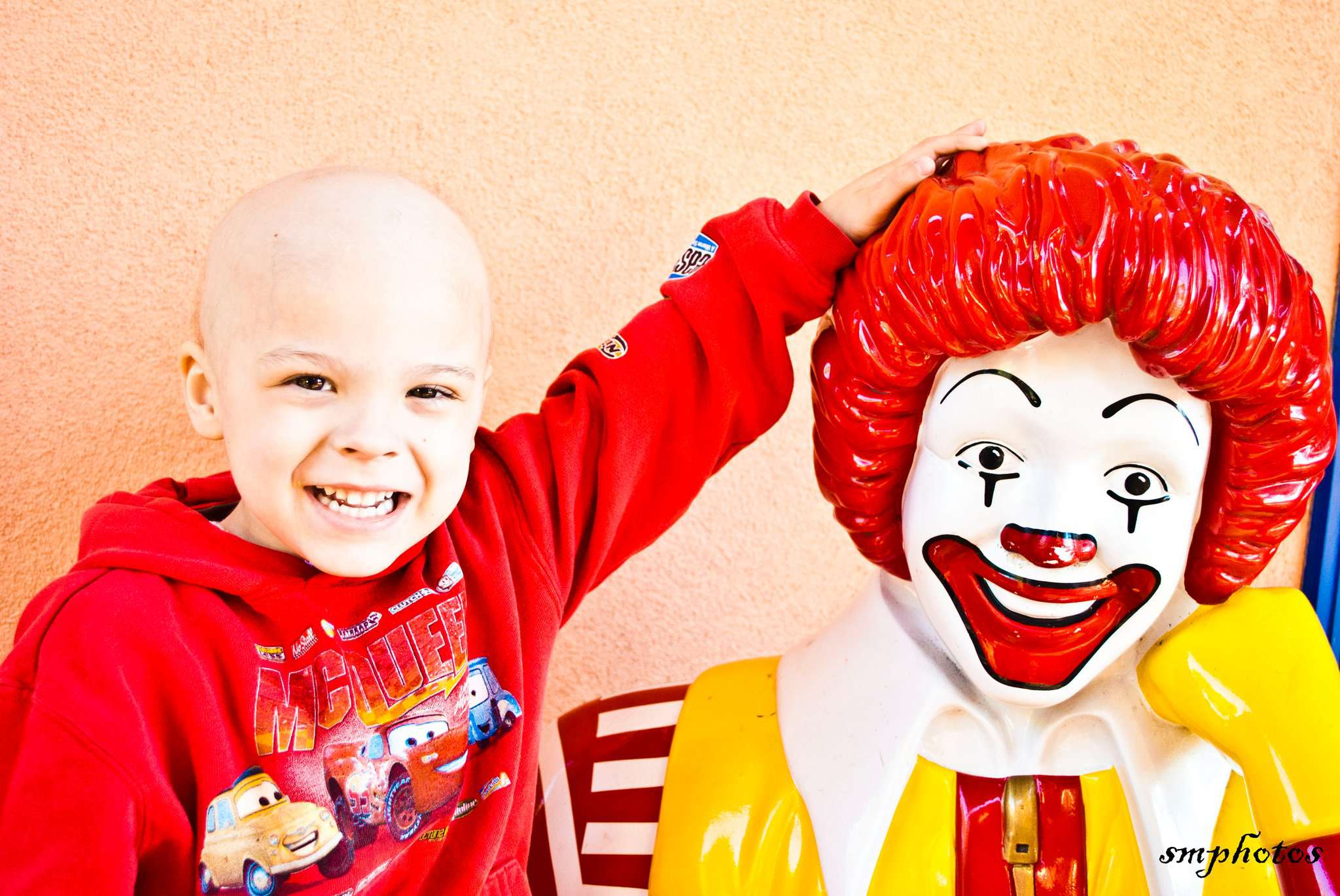 Young chemo patient posing with Ronald McDonald