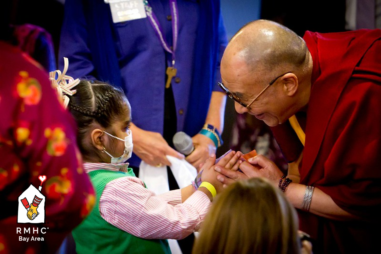 Dalai Lama holding hands of a patient during his visit to Ronald McDonald House in 2010 to speak with families.