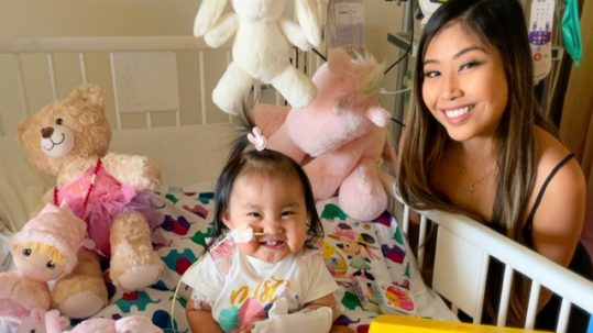 Smiling little girl in hospital bed and woman smiling next to the bed.