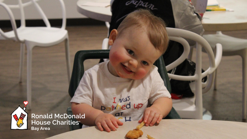 RMH baby eating nuggets at dinner and smiling