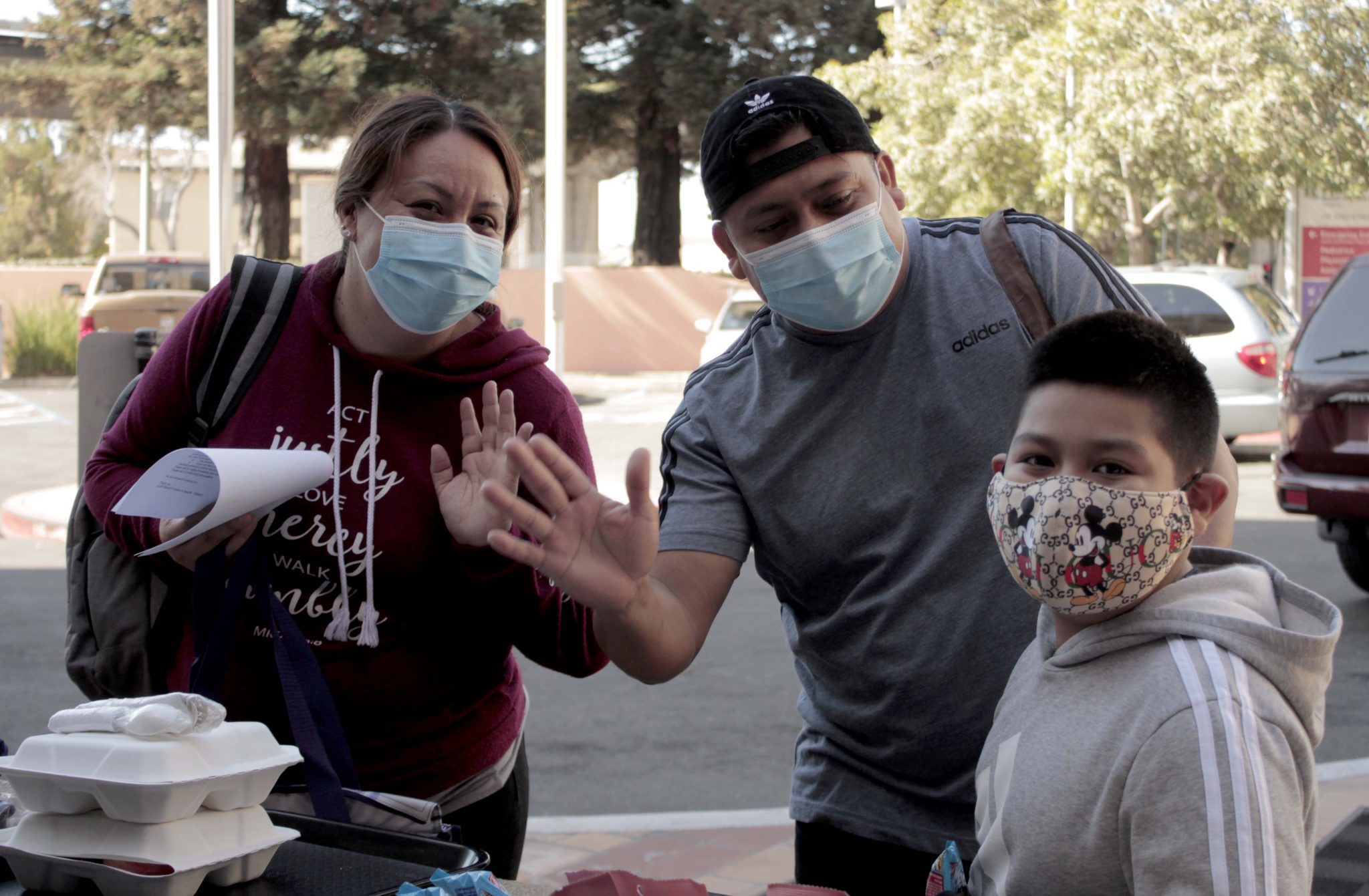 Family waving with masks on