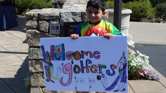 """Child smiling and holding """"Welcome Golfers"""" sign"""