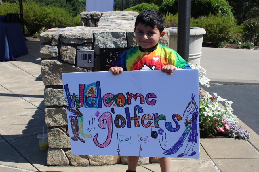 "Child smiling and holding ""Welcome Golfers"" sign"