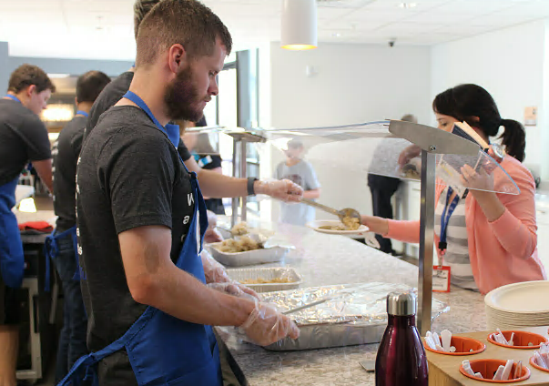 Volunteers serve a meal to a family