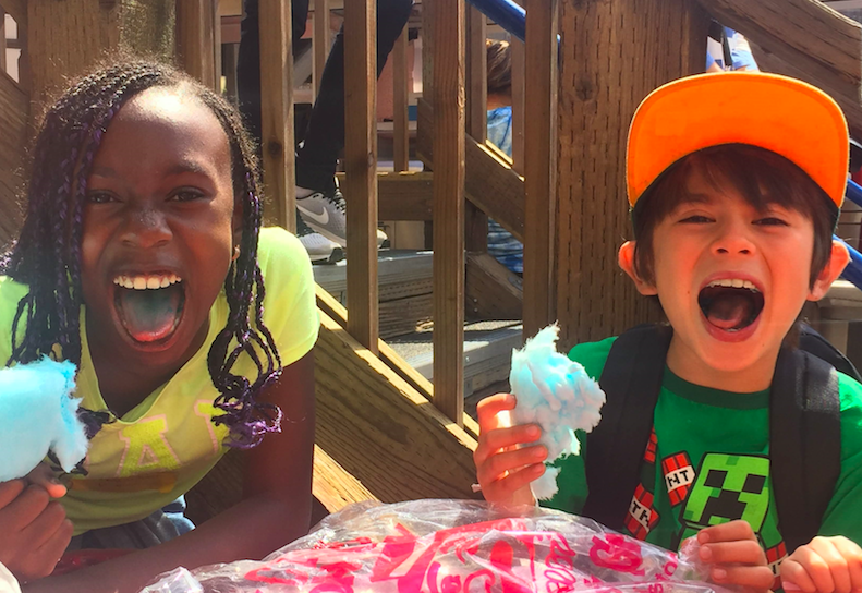 Two kids act silly while holding cotton candy at Siblings Camp